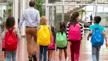 children in different colored backpacks walking