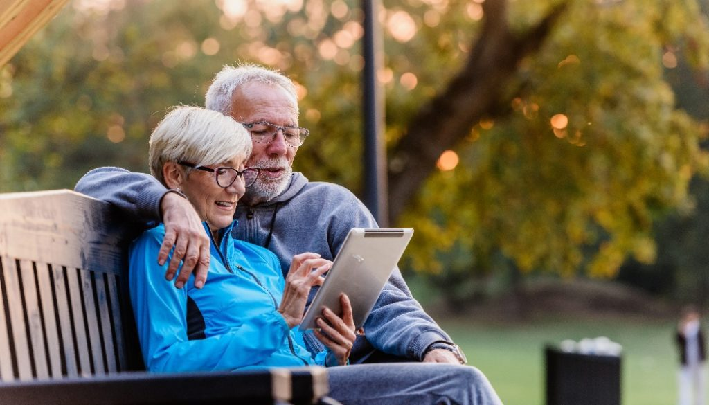 elderly couple sitting together on bench