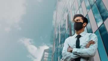 man wearing mask in front of office building